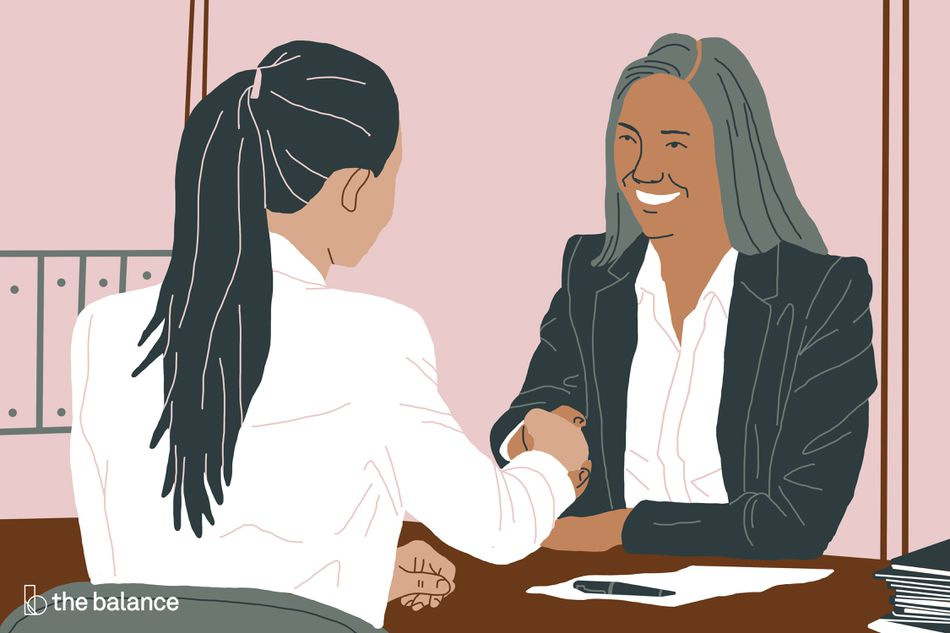 No text. Two women shaking hands over a desk, with a piece of paper and a pen beneath them.
