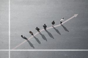 Overhead view of members of a working team standing on an ascending arrow-line.