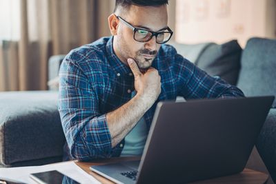 Man looking for work at home on laptop