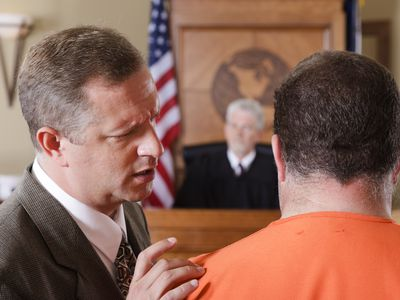Accused criminal and lawyer in a courtroom in front of judge