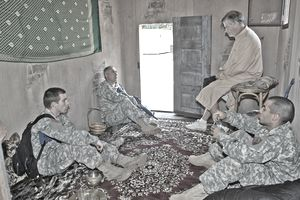 Men in fatigues and desert camouflage with persian rugs