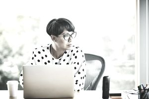 Portrait of mature businesswoman working on laptop at workstation in office