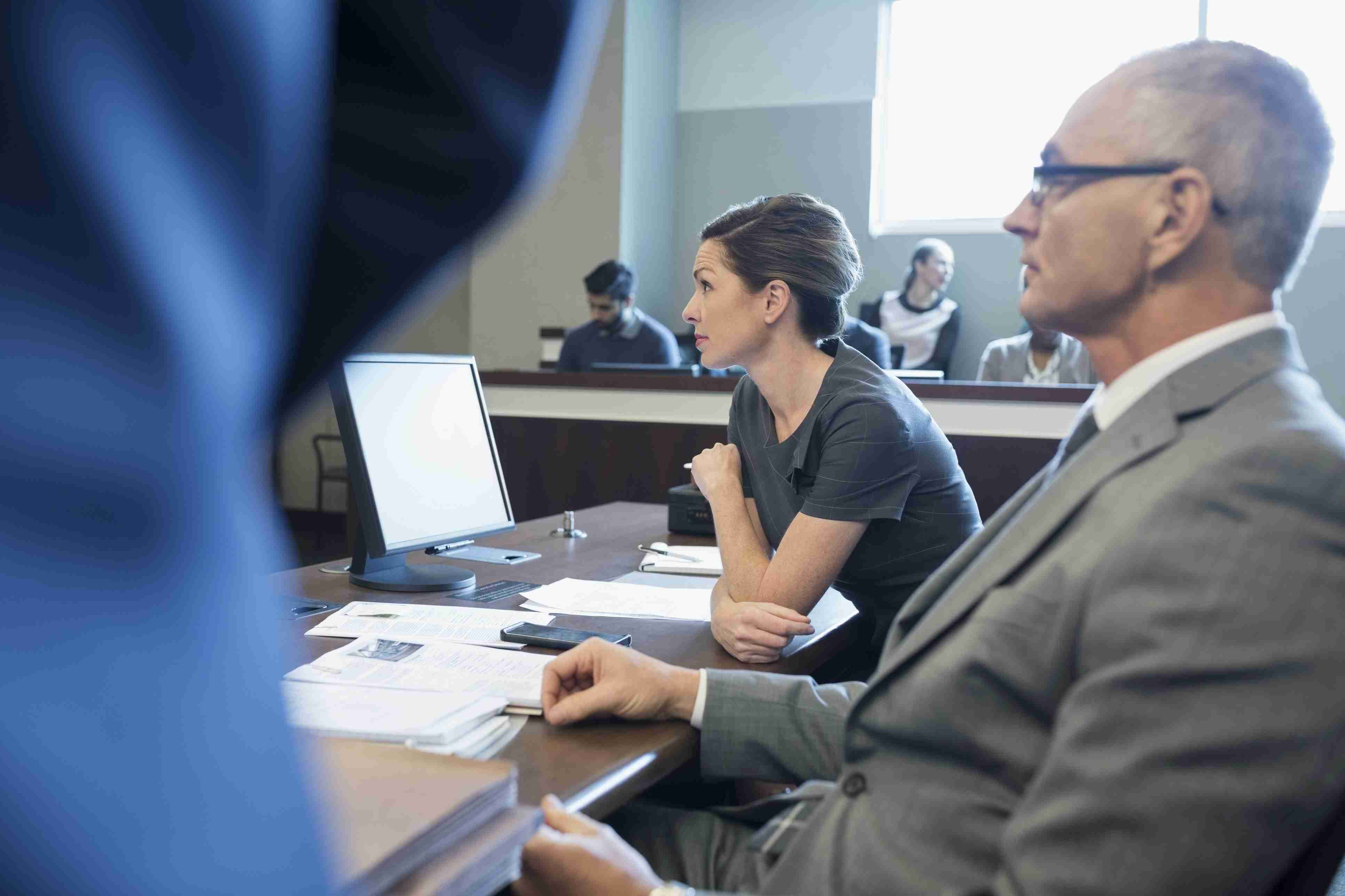 Attentive attorneys listening at table in legal trial courtroom