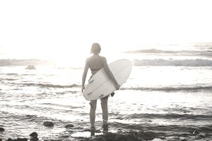 Woman with surfboard on rocky beach