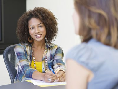 Woman in business casual clothing leading an interview.