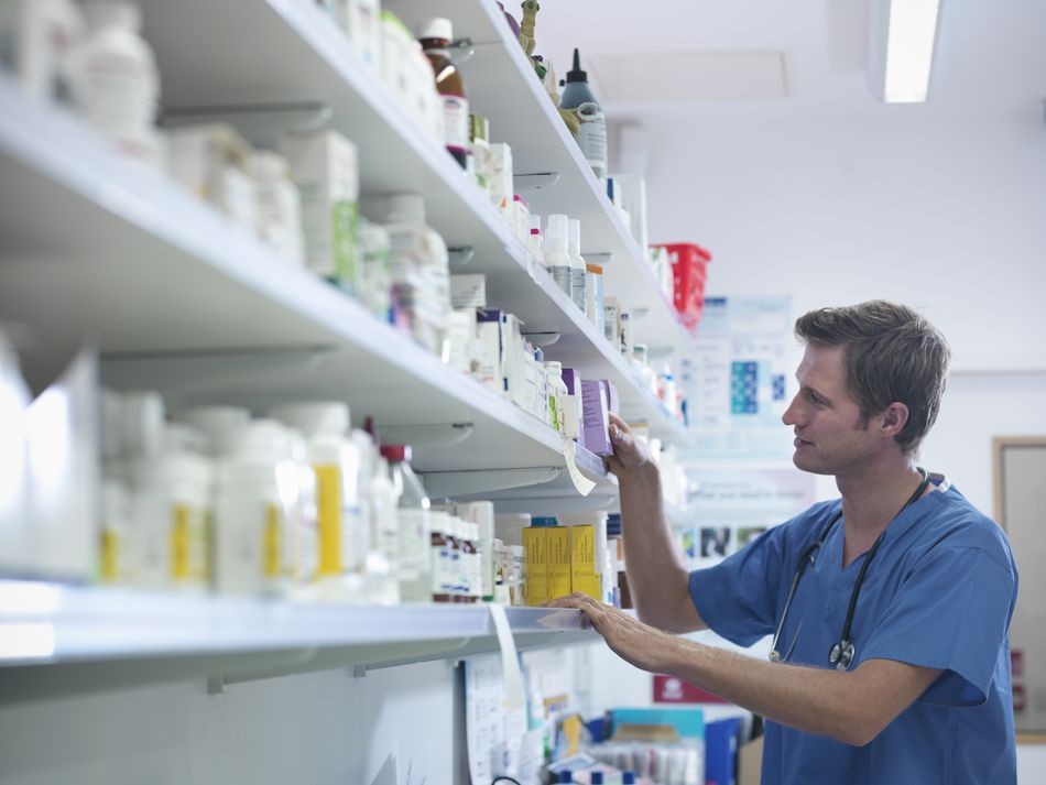 Doctor selecting medications from shelf in veterinary pharmacy