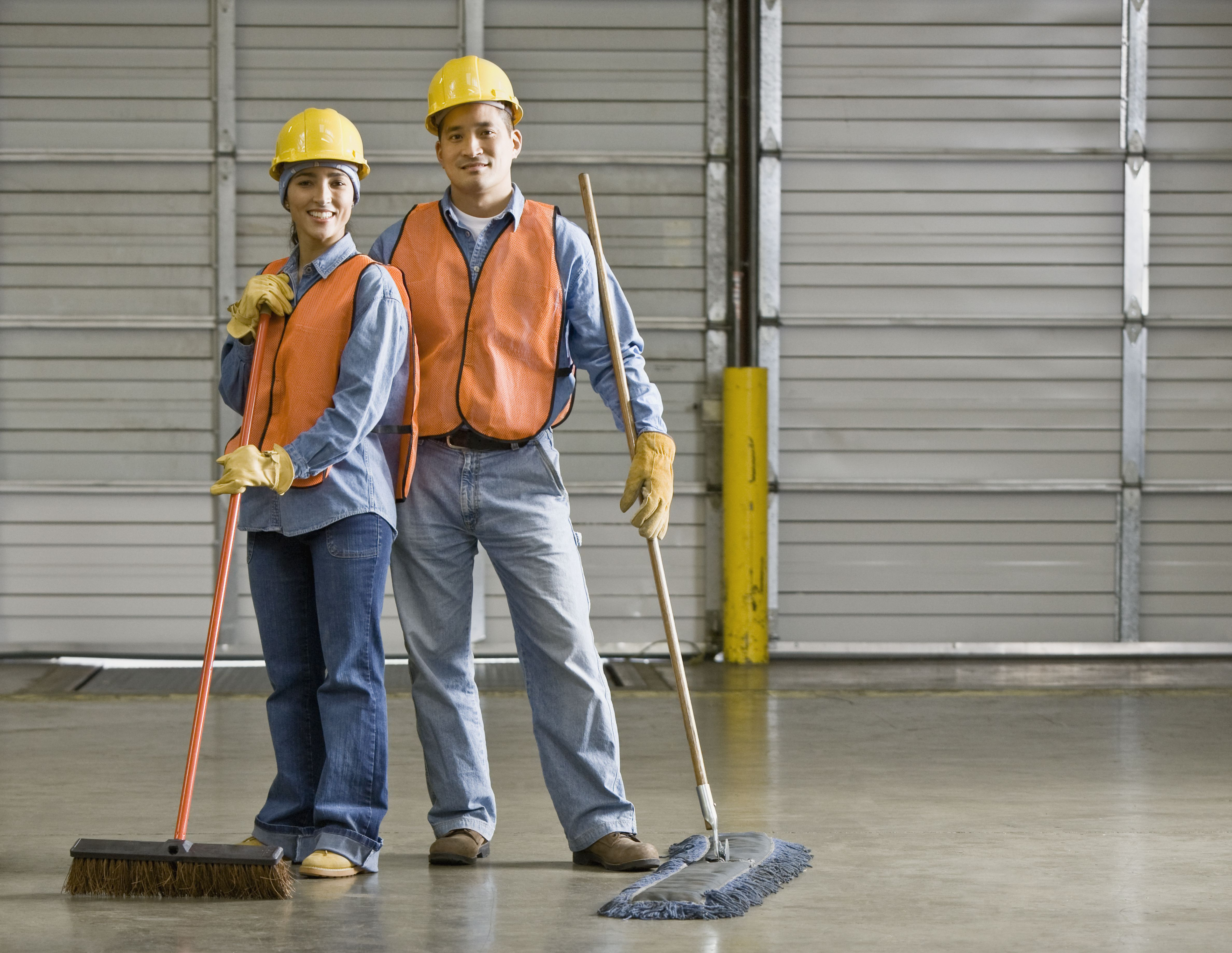 Warehouse workers holding brooms