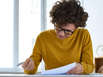 Woman sitting at desk and filling document while preparing tax papers