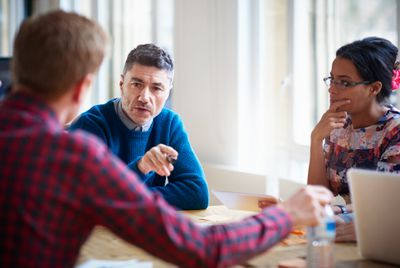 Three people at a table having a business meeting