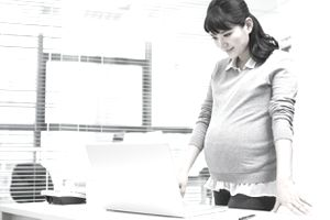 Pregnant woman standing at her desk reading over her client maternity email before she sends it.