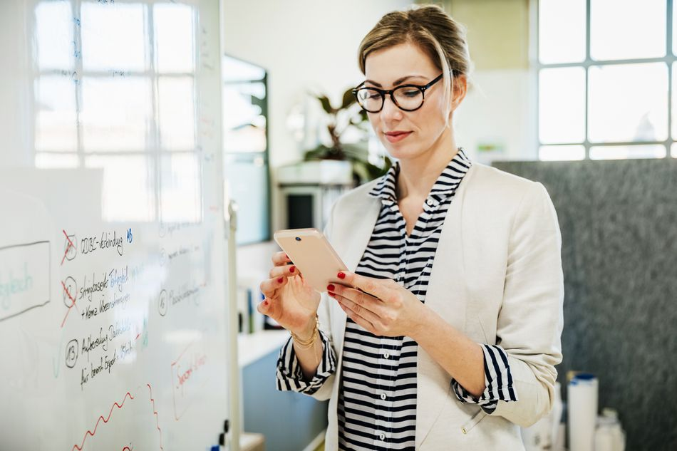 Businesswoman At The Office Using Smartphone