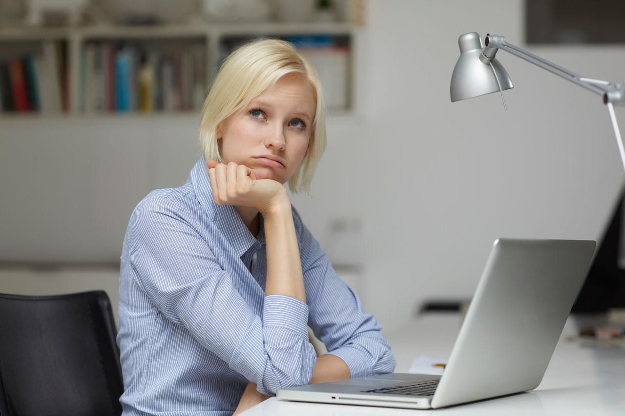 Pensive woman in front of computer