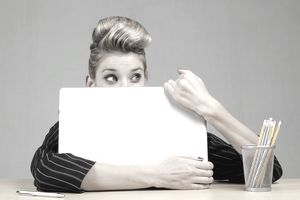 A woman hiding her face behind a laptop.