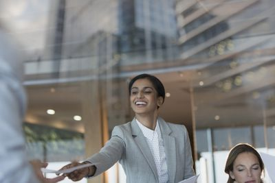 Smiling businesswoman handing paperwork to colleague in conference room meeting