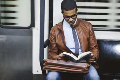 Young man reading a book on a train