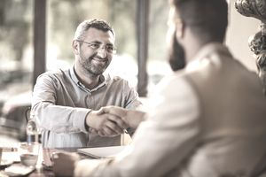 Smiling businessman shaking hands with his coworker in a cafe.