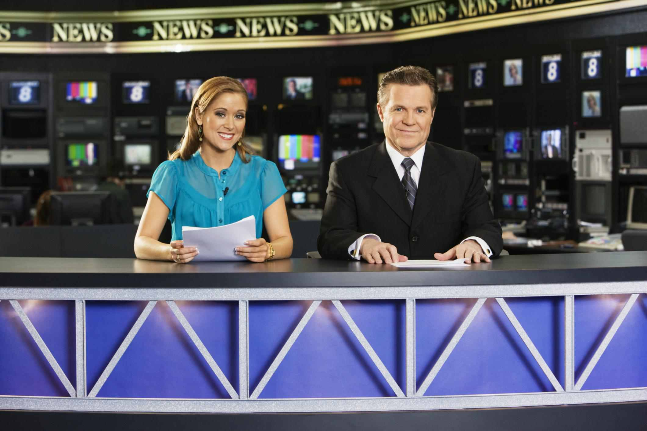 Two newscasters sitting at desk