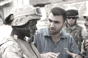 An Iraqi civilian speaks through a translator to the Marines