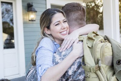 A young woman hugs a young man returning from Air Force basic training with a backpack on his back in front of a home.
