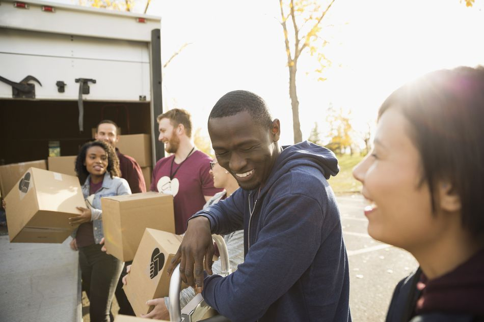Smiling volunteers unloading cardboard boxes from truck