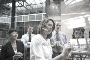 Businesswoman with dry erase marker writing on glass - stock photo
