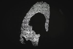 man is seen using a mobile phone in the light of a projection of a thumbprint