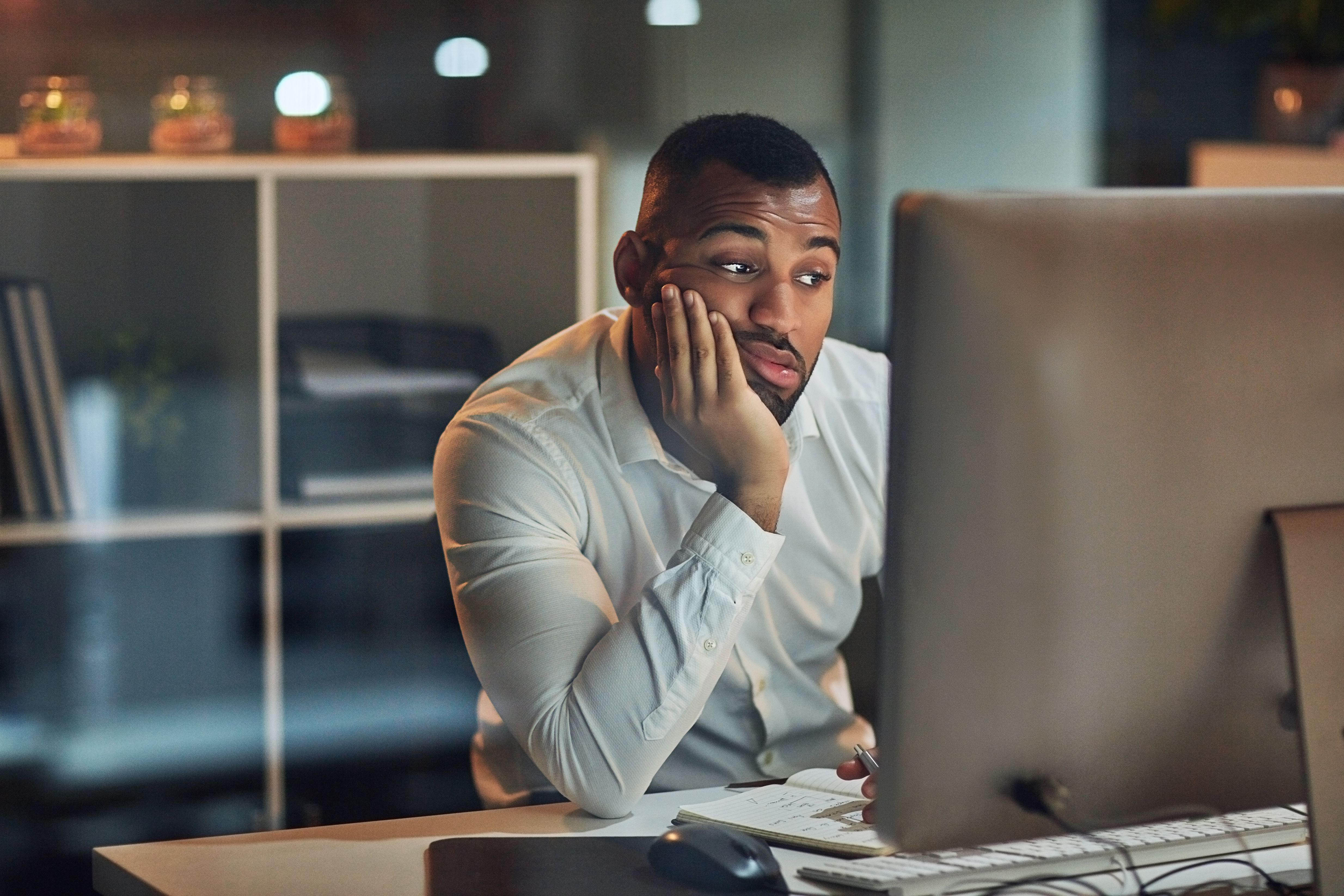 Man looking at computer screen resting his chin in his hand.