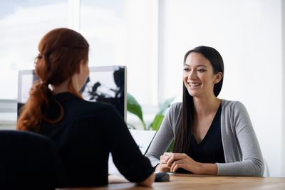 Two employees sitting across a table from each other speaking and building emotional intelligence which leads to efficiency.