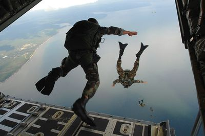 air force personnel air dropping into an ocean