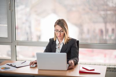 Woman working on laptop adding references to a job application.