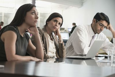 Business professionals in a meeting looking bored