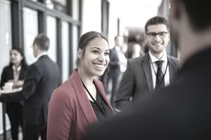 A young business woman is wearing a red blazer and black shirt. She is smiling and talking to colleagues.