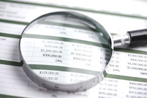 Financial spreadsheet with magnifying glass