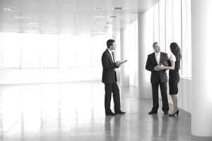 business people conversing in an empty office space