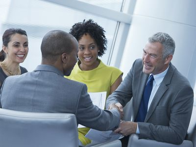 business people sitting in a circle chatting, two men shaking hands