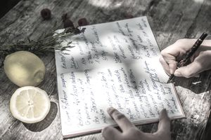 Close up of a woman writing a recipe in her journal.