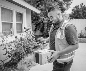 Young Male Delivery Man Takes Package to Home