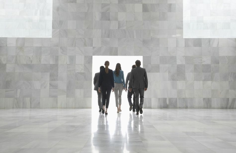 Business people walking toward doorway in modern lobby