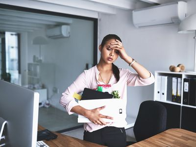 Shot of an unhappy businesswoman holding her box of belongings after getting fired from her job
