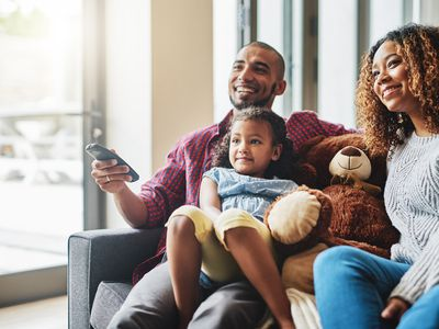 Young family watches television together.