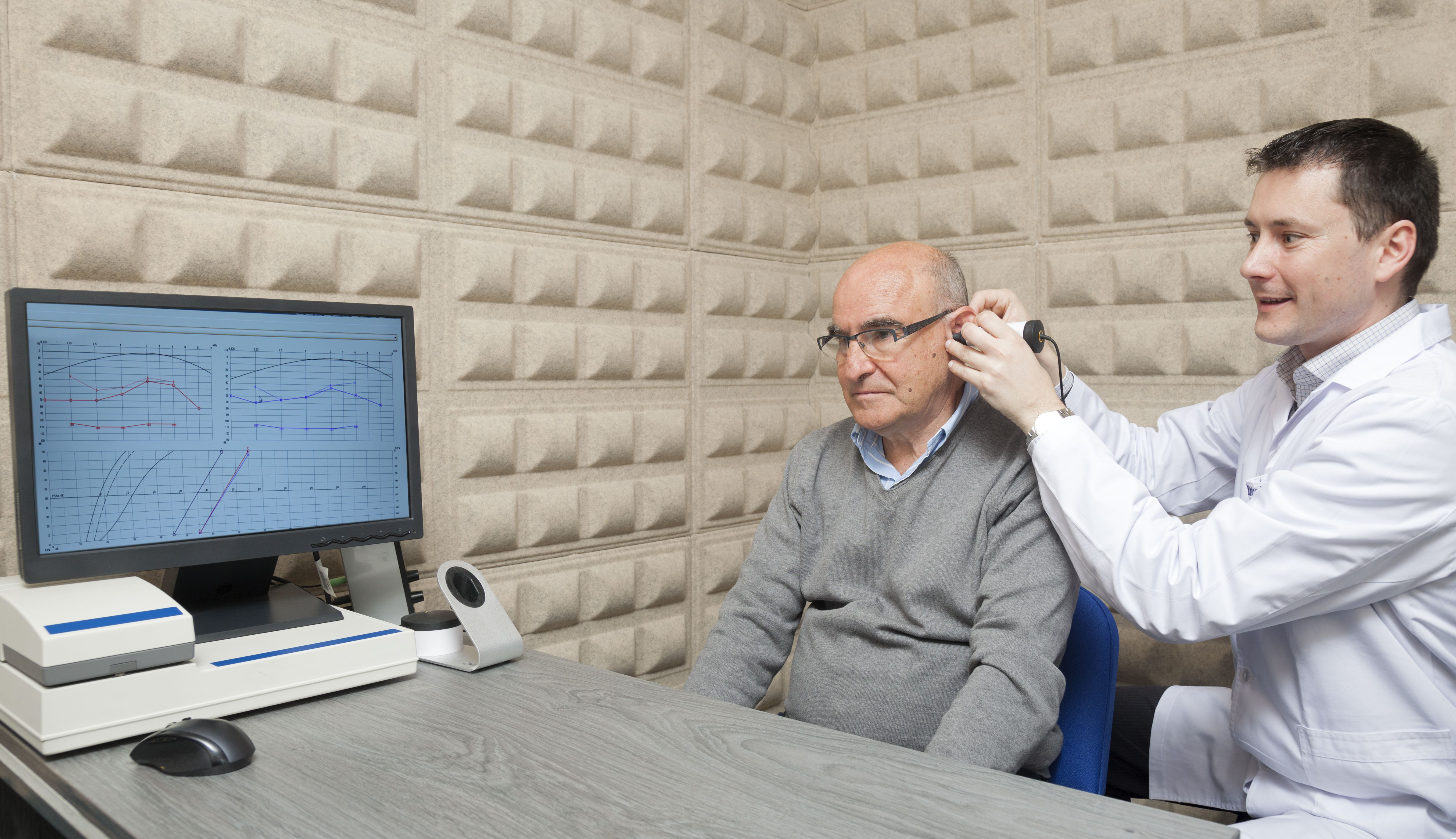 Audiologist checking a patient's hearing with a computer