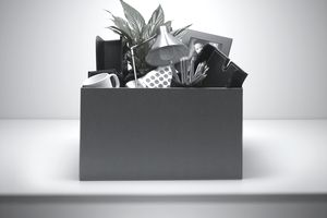 Box packed with desk objects representing a person being fired.