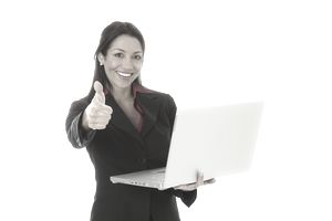 Businesswoman holding laptop and gesturing thumbs up to celebrate her sales commission.