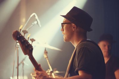 Bass player with drummer in background