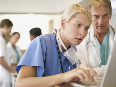 Nurse on computer with doctor looking over shoulder