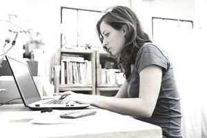 Young woman at laptop with bookshelves behind her