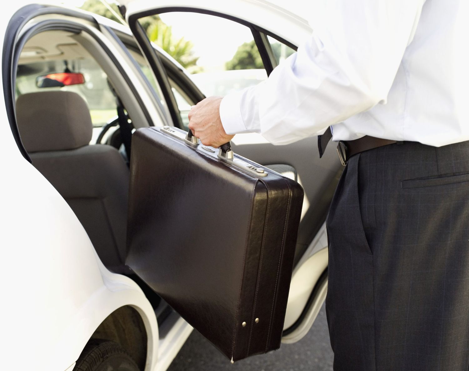 Man putting a briefcase into the backseat of a car.