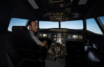 Asian male experiencing airplane cockpit