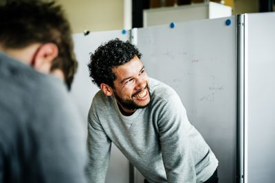 Black man in an office smiling at coworkers