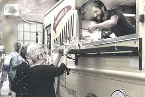 Man in food truck reaches serves two customers food